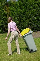 Woman tuging a garbage can