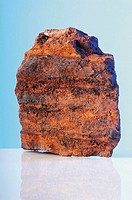 Geological rock, red, with layers, still life