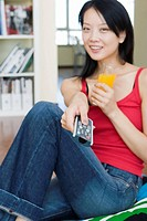 Young woman drinking orange juice and watching tv