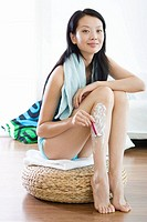 Young woman shaving legs, smiling
