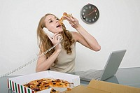 business woman eating pizza and answering telephone