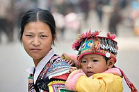 Hani mother with child in traditional hat, Shalatou market, Yuanyang, Yunnan, China. Children's hats in this part of China are imbued with much power....