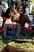 Women having her hair done on the market in front of vegetables