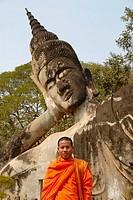 Buddhist monk wearing an orange robe in front of a Reclining Buddha statue, Buddha Park, Suan Xieng Khuan, near Vientiane, Laos, Southeast Asia