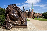 Sleeping lion, an iron sculpture in front of the historic Holstentor Gate, at back the steeple of the St. Petri church in the Hanseatic city of Luebec...