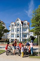 Family on bikes in front of the Dora Villa, sea front, Bansin, Usedom, Baltic Sea, Mecklenburg-Western Pomerania, Germany, Europe