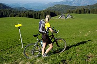 Blonde woman with a mountainbike walking on a meadow, view of the Ebenforstalm Alpine Pasture, Kalkalpen National Park, Upper Austria, Europe