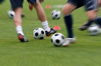 Footballs and the legs of FC Bayern Munich players during training