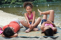 Young girl friends relaxing near lake