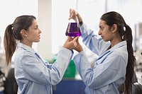 Scientists working in laboratory with beaker of liquid