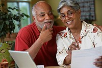 Senior African couple paying bills online