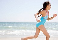 Hispanic girl running on beach