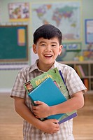 Asian boy holding schoolbooks in classroom