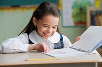 Hispanic girl looking at notebook in classroom