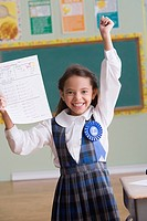 Hispanic girl holding A+ test paper in classroom