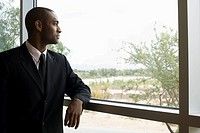 African businessman looking out window