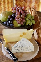 Brie and Emmanthaler (Swiss) on cheese cutting board with fruit and baguette