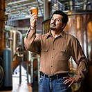 Hispanic man examining pint of beer in brewery
