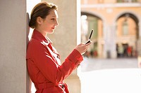 Businesswoman with cell phone leaning on pillar