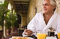 Smiling man in bathrobe at breakfast