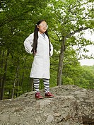 A girl scientist standing on rocks