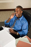 Businessman with paperwork on cell phone