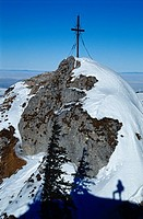 Shadow of a man in the snow under the summit cross of the Steinerner Jaeger Mountain, Reichraming, Upper Austria, Europe