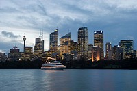 A boat and sydneys skyline at dusk