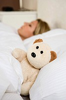 Woman in bed with teddy bear (thumbnail)
