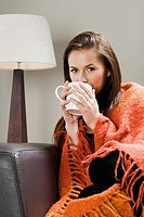 Woman with hot drink and blanket