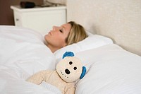 Woman in bed with teddy bear