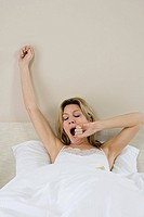 Woman in bed yawning