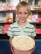 Portrait of a boy holding a tub of popcorn