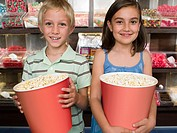 Two children holding tubs of popcorn