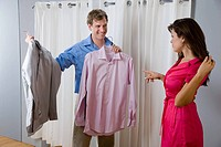 A woman helping a man choose a shirt