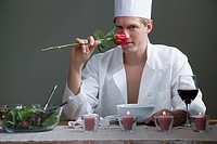 A man in chefs outfit smelling a rose and a romantic meal