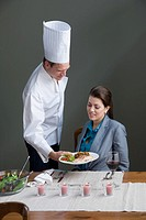A chef serving a woman with a meal