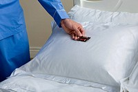 A man putting a chocolate on a pillow