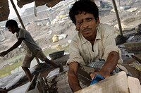 Many slum inhabitants live from recycling old industrial waste. Here daily paid workers are washing poisonous industrial slag searching for metal scra...