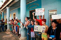 Cubans holding up signs advertising motels and Casa Particulares or home stay accommodation, during the arrival of a tourist bus at Vinales, Pinar del...