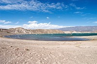 Panoramic view of high arid mountains behind the windswept Cuesta del Viento Reservoir Dam, Rodeo, San Juan Province, Argentina, South America