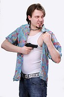 Young man with a goatee holding a gun, wearing an unbuttoned shirt over an undershirt, wifebeater