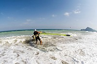 Windsurfer wearing helmet carrying his surfboard into the sea, Mediterranean coast, Spain