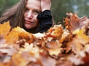 Woman surrounded by autumn leaves