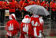 Adults and two children dressed up as harlequins, waiting in the rain for the start of the Carnival (Mardi Gras) parade in Duesseldorf, North Rhine-We...