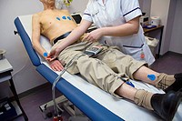 Heart monitoring. 93 year old patient undergoing an electrocardiography ECG examination. The electrodes attached to his chest are used to measure the ...