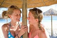 Teenage girls laughing under beach umbrella