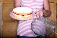 Close up of woman holding victorian sponge cake and colander (thumbnail)