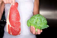 Close up of woman holding fresh meat and frozen broccoli