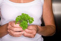 Close up of woman holding parsley